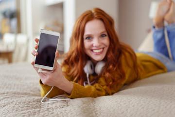 lachende frau liegt auf dem bett und zeigt ihr smartphone