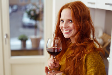 attraktive frau genießt ein glas rotwein zu hause