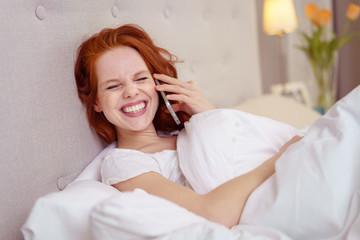 lachende frau telefoniert mit ihrem handy im bett