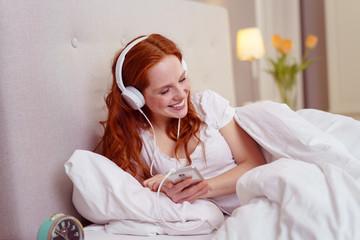 frau liegt im bett und hört musik