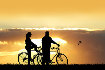 man and woman on a bicycle at sunset