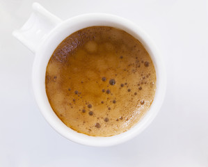Top view of a cup of coffee on white plate