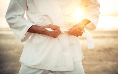 Karate fighter tying his kimono belt up