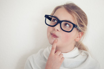 young girl with glasses thinking