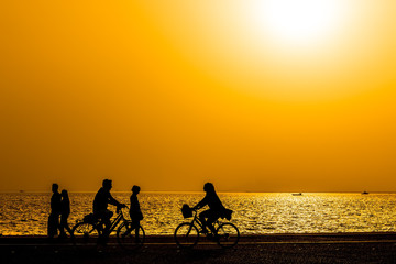 Silhouettes of people enjoying a walk by the seaside of the town