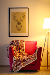 Pink armchair with blanket and lamp on light wall background