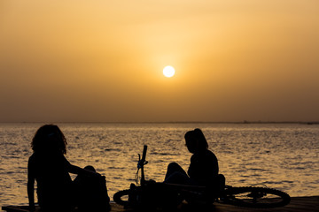 people relax on the waterfront at sunset