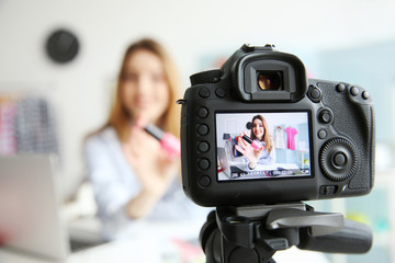 Young female blogger with nail polish on camera screen