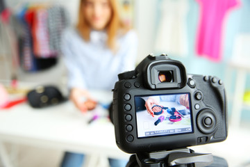 Young female blogger with makeup cosmetics on camera screen