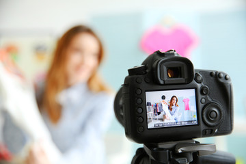 Young female blogger with white dress on camera screen