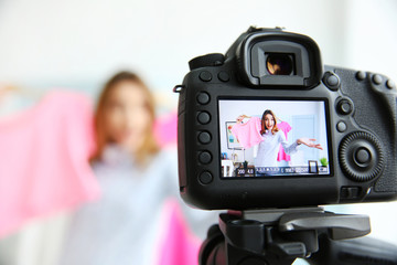 Young female blogger with pink shirt on camera screen