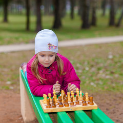 Little Girl playing chess outdoors on a park bench