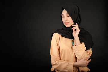 studio portrait of a young woman oriental appearance in the modern Muslim dress and covered her head against a dark background