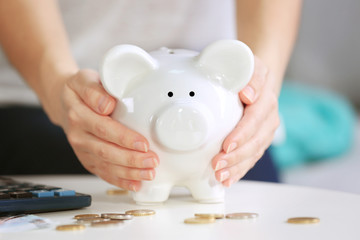 Female hands holding piggy bank on table closeup