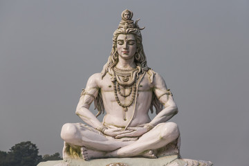 Hindu god Shiva sculpture sitting in meditation on Ganges river in Rishikesh, India, 2011 Wall mural