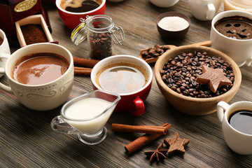 Delicious fresh coffee with spices on wooden table closeup