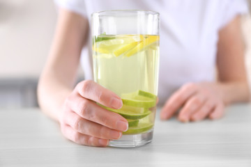 Female hand holding glass of lemonade closeup