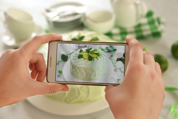 Female hands with smart phone making photo of a creamy lime cake closeup