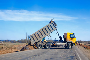 tipper unloads sand on the road. truck dumps sand on the side of the road during roadworks