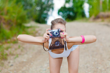 Hipster girl in shorts and a t-shirt with a vintage camera. modern hipster girl photographed using vintage camera. Outdoors lifestyle