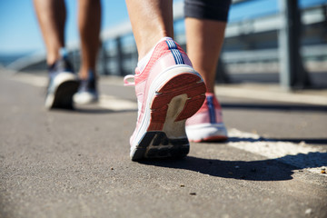 Feet of an athlete couple running on a pathway training for fitness and healthy lifestyle.