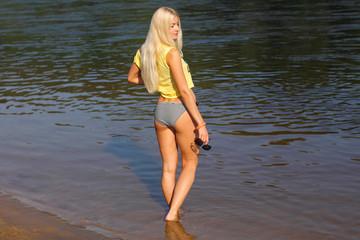 Woman walking on the beach. Beautiful woman legs, walking on the beach. Beautiful female legs go into the water