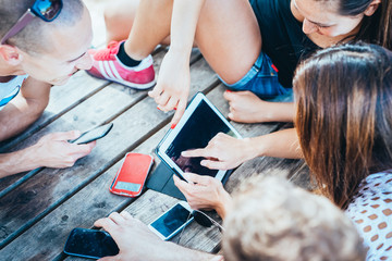 group of young multiethnic friends women and men at the beach in summertime using technological devices smart phone and tablet - social network, technology, communication concept