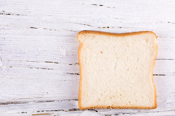 slice of toast on white wooden background
