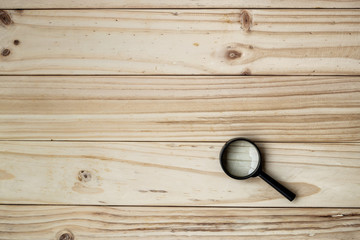 Magnifying Glass with Black Handle on the wooden background