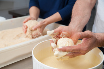 The making of sicilian arancini: sicilian cook diving a rice arancino into beaten eggs and flour