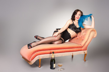 Cute retro pinup in black lingerie on vintage chaise