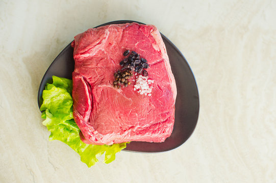Juicy red fillet beef steak on plate with pepper and green salad