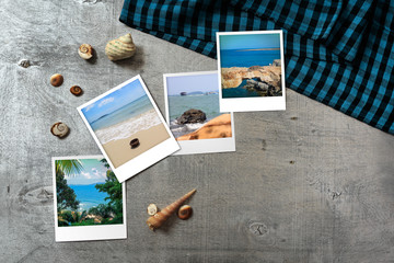 Beautiful seaside snapshots arranged on rustic wooden background with seashells around