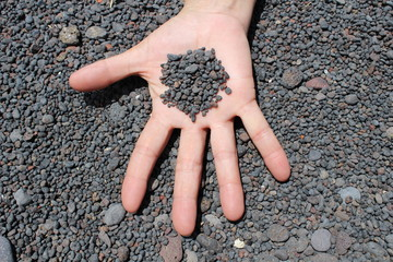 Granos de arena negra volcánica sobre la mano