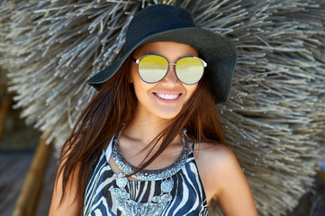 Beautiful happy girl in hat and sunglasses