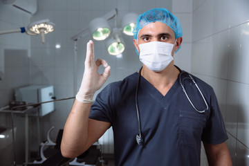 Surgeon man in operating room shows the sign OK