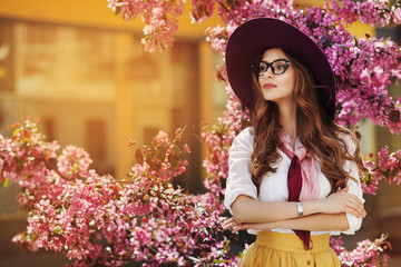 Outdoor portrait of young beautiful fashionable lady posing near flowering tree. Model wearing stylish accessories & clothes. Girl looking aside. Female beauty & fashion concept. City lifestyle. Toned