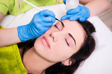 permanent eyebrow make up - beautician applying anesthesia and p