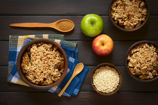 Baked apple crumble or crisp, spoonful of cinnamon powder, fresh apples and raw rolled oats on the side, photographed on dark wood with natural light