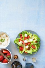 Green butterhead lettuce salad with baby mozzarella and strawberries