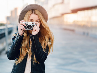 Beautiful and young girl in a hat and a camera walks and takes pictures