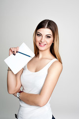 young positive smiling student girl with notebook and pen planning her daily schedule wearing casual white t-shirt on white. Studio retouched shot