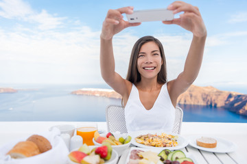 Wall Mural - Woman taking photo of breakfast using mobile cell smart phone app. Girl taking pictures of food on luxury travel vacation for social media. Beautiful female in resort in Santorini, Greece, Europe.