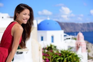 Wall Mural - Santorini tourist Thira Greece island tourism - Asian woman wearing red dress on summer travel looking at view with the famous attraction three domes chapel church. Luxury destination.