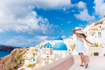 Wall Mural - Europe tourist travel woman in Oia, Santorini, Greece. Happy young woman looking at famous blue dome church landmark destination. Beautiful girl in white dress on visiting the Greek island.