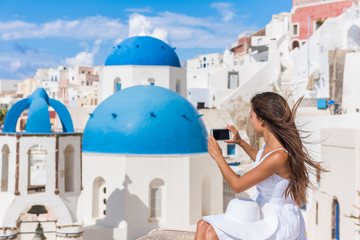 Wall Mural - Europe travel woman taking photo photographing using smart phone in Oia, Santorini, Greece. Famous blue domes on white church in village. Young asian tourist taking pictures on smartphone on holidays