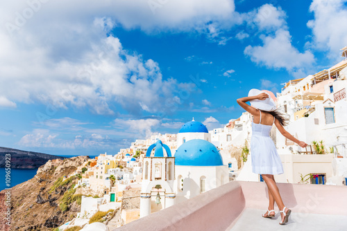 Wall mural Europe tourist travel woman in Oia, Santorini, Greece. Happy young woman looking at famous blue dome church landmark destination. Beautiful girl in white dress on visiting the Greek island.