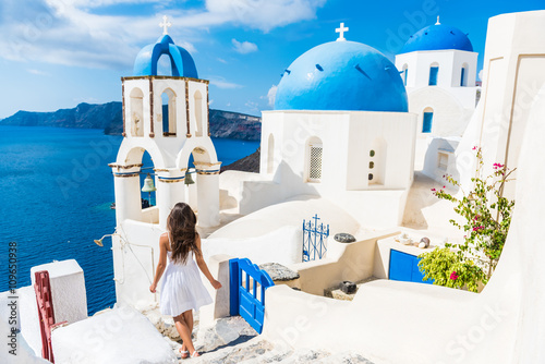 Wall mural Santorini travel tourist woman on vacation in Oia walking on stairs. Person in white dress visiting the famous white village with the mediterranean sea and blue domes. Europe summer destination.