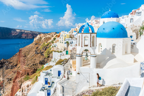 Wall mural Europe, Greek Islands, Greece, Santorini travel tourist vacation destination: City of Oia. Woman on holidays walking on stairs visiting the famous white village by mediterranean sea and blue domes.