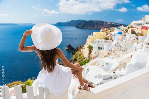 Wall mural Tourist woman enjoying view of beautiful white village of Oia with Caldera and mediterranean sea. Young stylish female model wearing sunhat and red dress enjoying summer travel vacation in Europe.